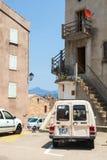 Het eiland van Corsica, de kleine mening van de stadsstraat met geparkeerde auto's Stock Foto