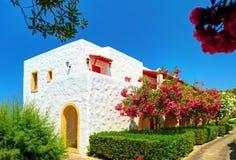 HET EILAND VAN KRETA, GRIEKENLAND, 01 JULI, 2011: Mening over Aldemar-hotelvilla onder kleurrijke bloemen voor toeristengasten Kl Stock Afbeelding