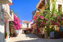 HET EILAND VAN KRETA, GRIEKENLAND, 06 SEP, 2012: Mening over kleine de stadsstraat van Panormo met van de koffie het rode bloemen Royalty-vrije Stock Foto's