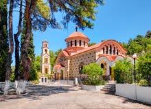 HET EILAND VAN RHODOS, GRIEKENLAND, JUN 28, 2015: Traditioneel Grieks kerkklooster Heilige Nektarios met klokketoren onder groene stock foto