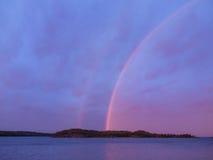 Het eilandlandschap van het avondmeer met dubbele regenboog Royalty-vrije Stock Foto's