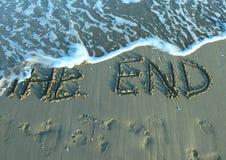 Het EIND op het strand door het overzees terwijl de golf komt Stock Foto
