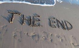 Het EIND op het strand wordt geschreven terwijl de golf die komt Royalty-vrije Stock Afbeeldingen
