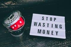 Het einde die uw geldbericht op lightbox met gambilng verspillen dobbelt geworpen in de bak stock fotografie