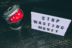 Het einde die uw geldbericht op lightbox met gambilng verspillen dobbelt geworpen in de bak stock afbeeldingen