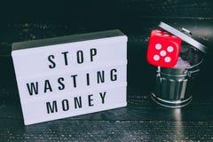 Het einde die uw geldbericht op lightbox met gambilng verspillen dobbelt geworpen in de bak royalty-vrije stock afbeelding
