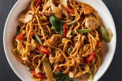 Het einoedels van het wok be*wegen-gebraden gerecht met gebraden kip en Thaise kruiden stock afbeelding