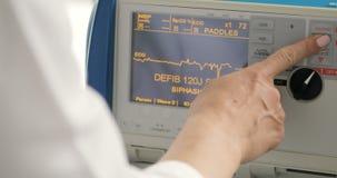 Het electrocardiogrammonitor van de artsencontrole in noodsituatieruimte bij het ziekenhuis stock videobeelden