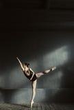Het elegante balletdanser uitrekken zich in de donkere aangestoken ruimte Royalty-vrije Stock Foto