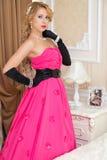 Het elegante blonde in lange rode kleding bevindt zich in de slaapkamer stock foto