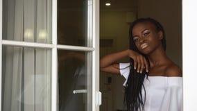 Het elegante glamour Afrikaanse vrouwelijke model kijkt zorgvuldig door het venster op de de flatsachtergrond van het luxehotel stock video