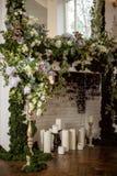 Het elegante grijze hoogtepunt van de baksteenopen haard van bloemen en kaarsen Elegante ruimte Huwelijk verfraaid gebied Uitstek stock afbeelding