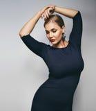 Het elegante jonge dame stellen op grijze achtergrond Royalty-vrije Stock Foto