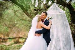 Het elegante jonge gelukkige huwelijkspaar zit bij groen gras Royalty-vrije Stock Afbeelding