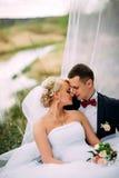 Het elegante jonge gelukkige huwelijkspaar zit bij groen gras Royalty-vrije Stock Afbeeldingen