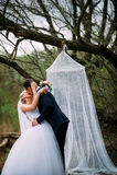 Het elegante jonge gelukkige huwelijkspaar zit bij groen gras Stock Foto's