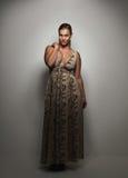 Het elegante jonge vrouw stellen in een avondtoga royalty-vrije stock foto's