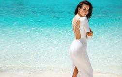 Het elegante jonge vrouw stellen op een tropisch strand stock fotografie