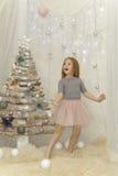 Het elegante meisje verheugt zich dichtbij een bont-boom Royalty-vrije Stock Foto's