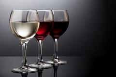 Het elegante rood, nam en witte wijnglazen op een zwarte achtergrond toe Stock Fotografie