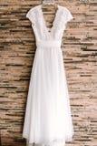 Het elegante witte huwelijkskleding hangen stock afbeeldingen