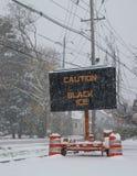 Het elektrische verkeer mobiele teken door de kant van een sneeuw behandelde weg met sneeuw dalende waarschuwing van ijzel op weg stock afbeelding