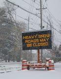 Het elektrische verkeer mobiele teken door de kant van een sneeuw behandelde weg met sneeuw dalende waarschuwing van zwaar sneeuw royalty-vrije stock fotografie