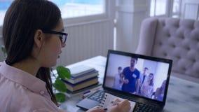 Het elektronische onderwijs, studente in oogglazen met pen schrijft in blocnote tijdens het letten op video op een notitieboekje stock videobeelden