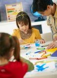 Het elementaire leeftijdsschoolmeisjes schilderen Stock Afbeeldingen