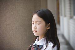 Het elementaire schoolmeisje bidden Stock Afbeeldingen