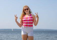 Het elf éénjarigenmeisje glimlacht en geeft tweezijdig overwinningsteken aangezien zij zich op Alki Beach, Seattle, Washington be stock fotografie