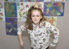 Het elf éénjarigenmeisje in humoristisch gemiddeld meisje stelt Stock Afbeelding
