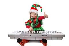 Het elf van de meisjeskerstman speelt een synthesizer Royalty-vrije Stock Fotografie
