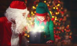 Het elf van Santa Claus en van het helperkind met heldere magische gift in Chr Stock Afbeelding