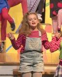 Het elfjaren oude meisje zingen op stadium in schoolspel Royalty-vrije Stock Foto's