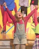 Het elfjaren oude meisje zingen op stadium in schoolspel Stock Afbeelding