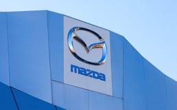 Het embleem Mazda op blauwe hemelachtergrond Stock Afbeeldingen