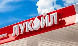 Het embleem van de oliemaatschappij Lukoil tegen de blauwe hemel Royalty-vrije Stock Afbeelding