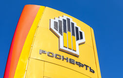 Het embleem van de oliemaatschappij Rosneft tegen de blauwe hemel backg Royalty-vrije Stock Afbeelding