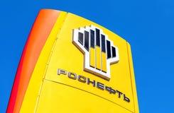 Het embleem van de oliemaatschappij Rosneft tegen de blauwe hemel backg Royalty-vrije Stock Afbeeldingen