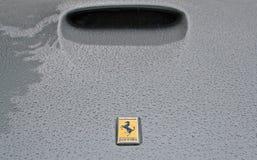 Het embleem van Ferrari op regenachtige bonnet stock foto's