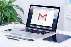 Het embleem van Google Gmail op de vertoning van Apple MacBook op bureau Stock Foto's