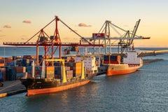 Het EmonaVrachtschip en het Vrachtschip van Renate P dokten bij de Haven van Barcelona bij zonsondergang stock afbeelding