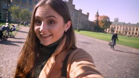 Het emotionele artistieke Kaukasische mooie meisje heeft videogesprek en bekijkt Webcamera terwijl het houden van het, het glimla stock videobeelden