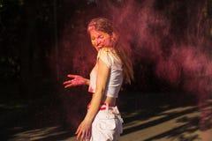 Het emotionele donkerbruine vrouw spelen met roze droge verf Holi explod Royalty-vrije Stock Foto