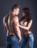 Het emotionele jonge paar stellen in modieuze jeans Stock Afbeeldingen