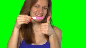 Het emotionele meisje die zwangerschapstest met twee strepen tonen en bekijkt camera stock video