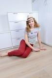 Het emotionele meisje zit op een vloer en stelt in een hoed stock foto's