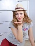 Het emotionele meisje zit op een vloer en stelt in een hoed stock fotografie