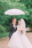 Het emotionele portret van de vrolijke jonggehuwden die onder de paraplu in het de lentepark lopen Royalty-vrije Stock Afbeelding